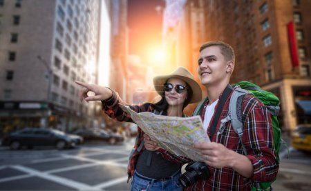 Travelers with backpacks looking for city attractions on the map, excursion in tourist town. Summer hiking. Hike adventure of young man and woman