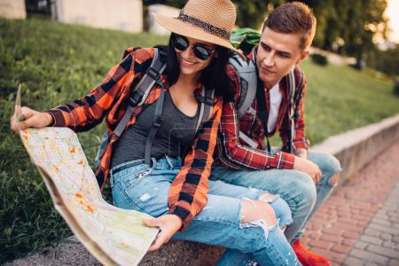 Photo for Couple of tourists study the map of attractions, excursion in town. Summer hiking. Hike adventure of young man and woman - Royalty Free Image