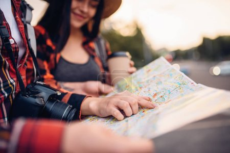 Photo pour Touristes étudient le plan des attractions de la ville, excursion dans la ville. Randonnée de l'été. Randonnée aventure du jeune homme et femme - image libre de droit