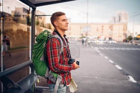 Photo for Male tourist with backpack at bus stop. Summer travelling, hike adventure over sightseeing, city walking - Royalty Free Image