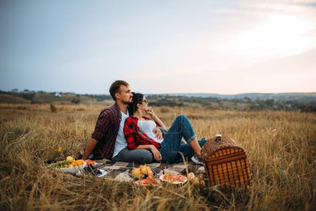 Photo for Love couple, picnic on plaid in summer field. Romantic junket of man and woman - Royalty Free Image