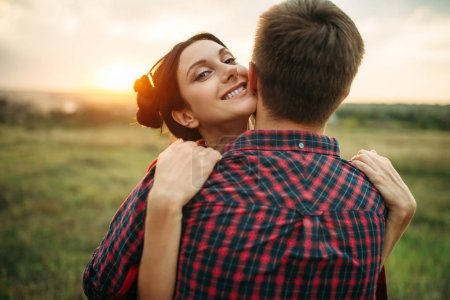 Love couple hugs together on the meadow at sunset. Romantic junket of man and woman, picnic in the field