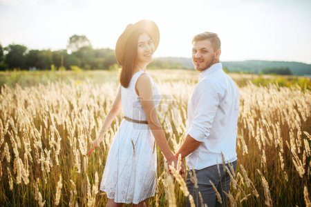 Love couple hold hands, walking in a rye field. Cute family on summer meadow