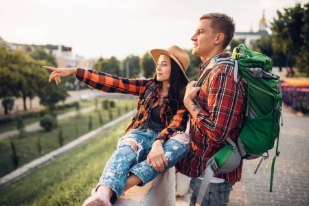 Photo for Hikers with backpacks go sightseeing in tourist town on vacation. Summer hiking. Hike adventure of young man and woman - Royalty Free Image