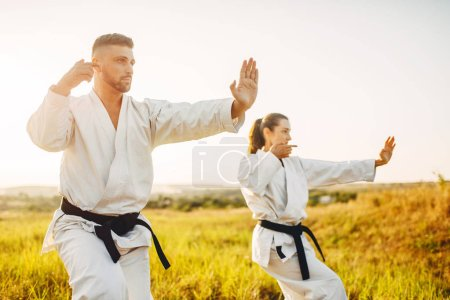 Male and female karate masters with black belts fight in summer field. Martial art fighters on training outdoor, technique practice
