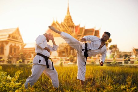 Karate fighters on training fight against ancient temple on sunset. Martial art workout outdoor. Photo manipulation with background