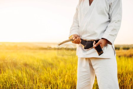 Male karate fighter in white kimono with black belt, summer field on background. Martial art training outdoor