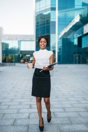 Photo for Business woman with cardboard coffee cup and notepad outdoors, office building on background. Black businesswoman in skirt and white blouse - Royalty Free Image