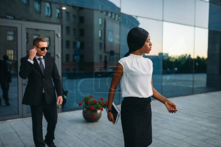 Photo for Black business woman bodyguard in suit and sunglasses on background. Security guard is a risky profession, protection of VIPs, guarding occupation, private safety - Royalty Free Image