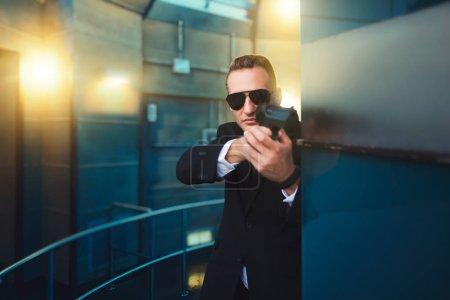 Photo pour Garde du corps en costume et lunettes de soleil avec une arme à feu dans ses mains. Security guard est une profession risquée, de professionnel de gardiennage, de politiciens et de protection de personnes entreprise contre le danger de la vie - image libre de droit