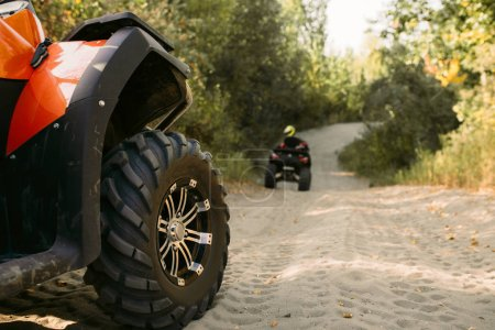Two riders on quad bikes having offroad adventure in forest. Riding on atv, view from the wheel, extreme sport and travelling