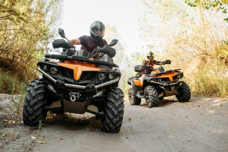Two quad bike riders in helmets travels in forest, front view. Riding on atv, extreme sport and travelling, quadbike adventure