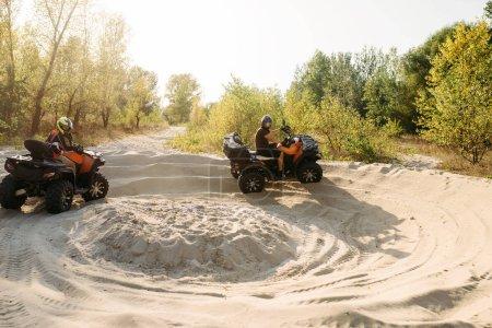 Photo pour Deux conducteurs de VTT en casques courir tours sur sable, offroad en forêt. Équitation sur Quad, sport extrême et voyage, aventure Quad - image libre de droit