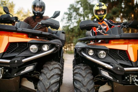 Two riders in helmets and equipment on quad bikes, front view, closeup. Male quadbike drivers, atv riding, extreme sport
