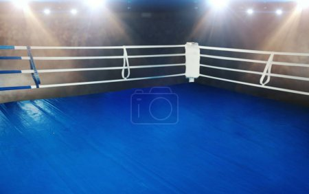 Boxing ring with blue flooring and white ropes. Professional arena for sport competitions and fighting tournaments