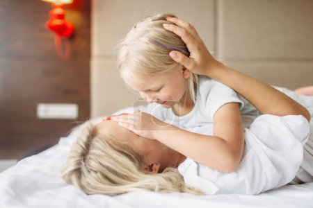 Cheeful mother and child plays hide and seek lying on the bed at home. Parent feeling, togetherness, motherhood