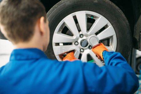 Photo pour Mécanicien dévisse roue de voiture, pneu service. Réparation automobile, entretien des véhicules - image libre de droit