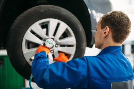 Mechanic unscrews car wheel, tire service. Automobile repair, vehicle maintenance