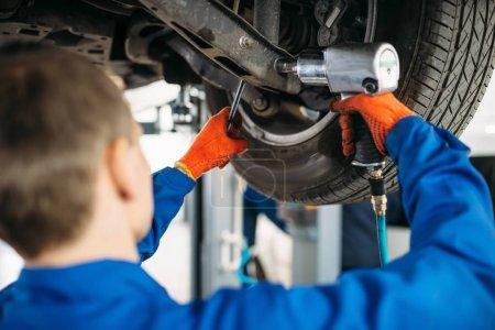 Techniker mit einem Schraubenschlüssel reparieren die Federung, Auto auf der Hebebühne. Autoservice, Fahrzeugwartung