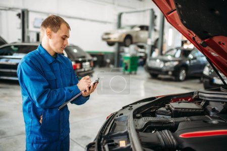 Photo for Technician with notebook fills the check list, car with opened hood, fixing the problems. Automobile service, vehicle maintenance - Royalty Free Image