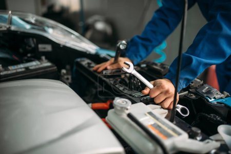 Male technician works with car engine. Auto-service, vehicle maintenance, repairman with tools