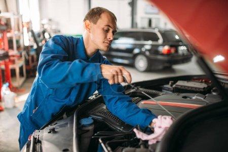 Male technician checks car engine oil level with dipstick. Auto-service, vehicle maintenance, repairman