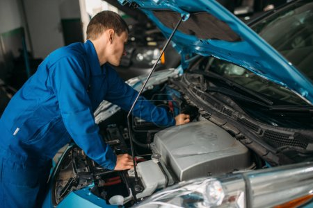 Mechanic repairs car engine, motor diagnostic. Car with opened hood, auto-service