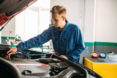 Mechanic connects air conditioning system for diagnosis of freon. Conditioner diagnostic