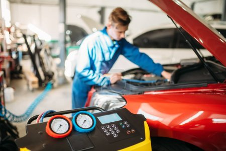 Photo for Mechanic pumps freon into the car air conditioning system. Conditioner inspection in auto-service - Royalty Free Image