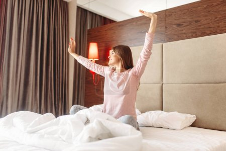 Photo for Young woman wake up in the morning, stretching in the bed, bedroom interoir on background - Royalty Free Image