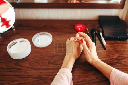 Photo pour Jeune femme s'applique la crème pour les mains à la peau. Procédure de soins de la peau matin - image libre de droit