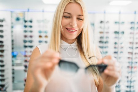 Photo for Female optician shows sunglasses in optics store. Selection of eyes protection with professional optometrist, optometry concept - Royalty Free Image