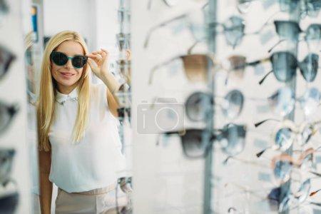 Femme client essaie des lunettes de soleil dans le magasin d'optique, vitrine avec des lunettes sur fond. Sélection de protection des yeux dans la boutique de lunettes, concept d'optométrie