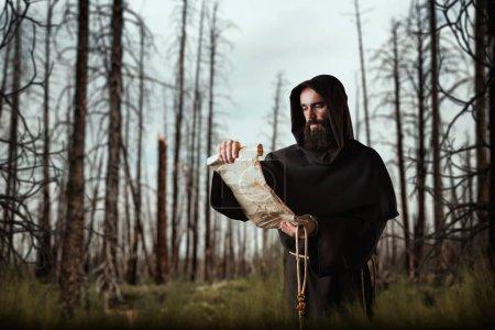 Photo pour Un moine médiéval au visage maléfique lit une prière dans l'ancien manuscrit de la forêt - image libre de droit