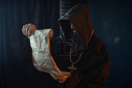 Photo pour Moine médiéval avec un visage mal lu une prière dans l'ancien manuscrit, religion. Mystérieux moine dans cape sombre. Mystère et spiritualité - image libre de droit