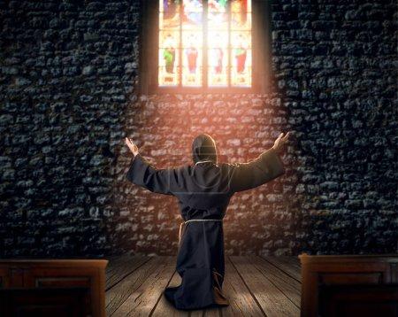 Photo pour Moine médiéval s'agenouiller et de prier contre une fenêtre dans l'église, arrière, vue, religion. Mystérieux moine dans cape sombre. Mystère et spiritualité - image libre de droit