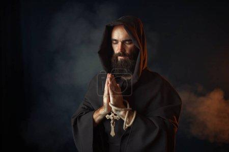Photo pour Moine médiéval dans une robe noire avec capuche prier avec fermé les yeux, rituel secret. Mystérieux moine dans cape sombre. Mystère et spiritualité - image libre de droit