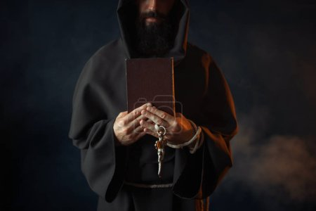 Photo for Medieval monk holds book and wooden cross in hands, secret ritual. Mysterious friar in dark cape. Mystery and spirituality - Royalty Free Image