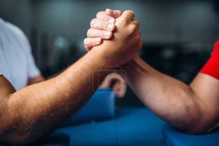 Photo pour Rejoint les mains musclées masculines à la table avec des broches, concept de lutte. Défi de lutte. Prêt, partez - image libre de droit