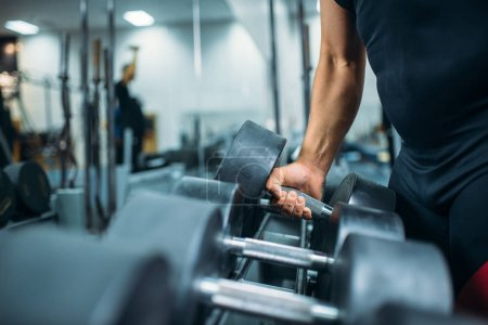 Photo for Male athlete takes heavy dumbbell in hand, gym interior on background. Weightlifting workout in sport or fitness club, weight choosing concept - Royalty Free Image