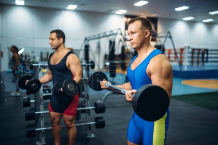 Photo for Strong male athletes works with weights in gym. Weightlifting workout in sport or fitness club - Royalty Free Image