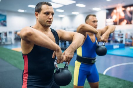 Strong male lifters doing exercise with kettlebell...