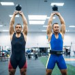 Two male lifters lifted kettlebells over thier hea...