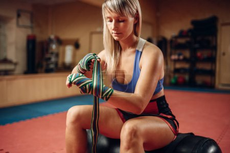 Photo for Female kickboxer in boxing bandages and sportswear sitting on punching bag after workout in the gym. Woman boxer on training, kickboxing practice - Royalty Free Image
