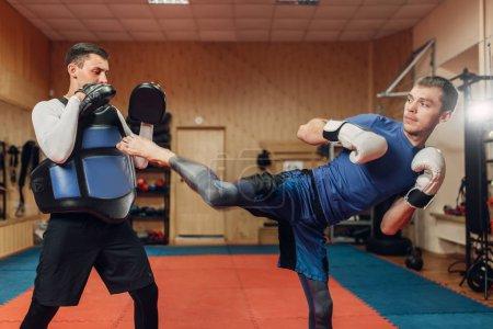 Photo pour Kickboxer homme pratiquant le coup avec un entraîneur personnel, d'entraînement en gymnase. Boxer frappe sur la formation, la pratique du Kick-Boxing - image libre de droit