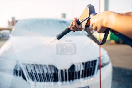 Photo for Female person wash off the foam from the car. Young woman on self-service automobile washing. Outdoor vehicle cleaning - Royalty Free Image