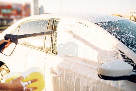 Foto de Mano de persona de sexo femenino con esponja lavado de vehículo con espuma, lavado de coches. Mujer joven en autoservicio lavado de automóviles. Lavado de autos al aire libre en verano - Imagen libre de derechos