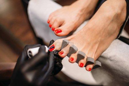 Photo pour Master de pédicure en couverture de gants noirs avec les ongles de pied polonais de clientes, vue, salon de beauté. Soin des ongles professionnel - image libre de droit