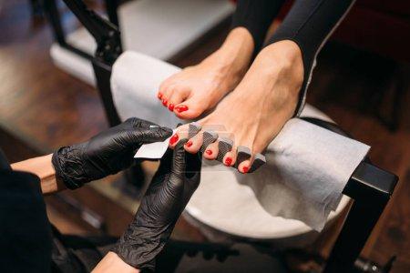 Photo pour Pedicure master en gants noirs polit les ongles avec une lime, cliente dans le salon de beauté. Soins des ongles professionnels - image libre de droit