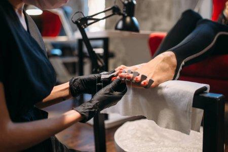 Photo pour Master de pédicure en gants noirs vernis ongles avec une lime, clientes dans un salon de beauté. Soin des ongles professionnel - image libre de droit